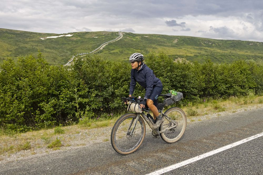 The Trans-Alaska Pipeline snakes endlessly behind Lael Wilcox as she rides the Richardson Highway near Paxon on Friday, July 16, 2021. (Photo by Rugile Kaladyte)