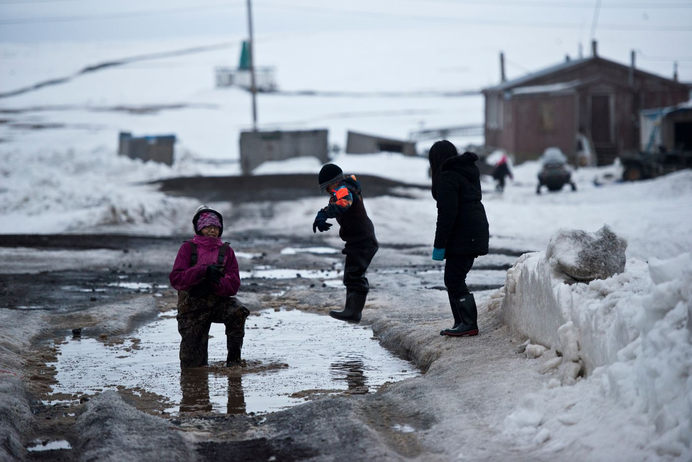 Children play in a puddle in Savoonga last month. (Marc Lester / Alaska Dispatch News)