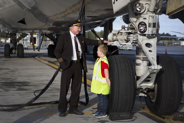 UPS Captain Mark Jerman compares Tyler Blades, 6, to the size of a Boeing 747 cargo aircraft wheel Friday, September 8, 2017, in Anchorage. Jerman and Tyler met while seated next to each other during a red-eye flight early August. Despite having just flown behind the controls for ten hours from Hong Kong to Anchorage, Jerman answered all of Tyler's questions about flying and airplanes. Cheryl Blades, Tyler's mother, contacted UPS to thank Jerman for his time. Tyler and his family were invited to tour a UPS 747 freighter. (Rugile Kaladyte / Alaska Dispatch News)