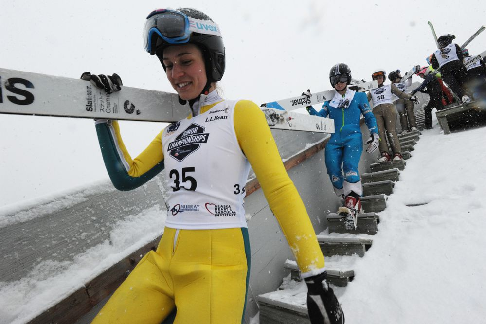 Sophia Nester of Park City carries her skis as she walks down from a tower at the Karl Eid Ski Jumping Complex at Hilltop Ski Area on Thursday, Feb. 22, 2018 after heavy snowfall forced officials to cancel the first day jumping for safety concerns. The Ski Jumping / Nordic Combined Junior Nationals comes to Anchorage every five years and more than 50 of the nation's best young ski jumpers and nordic combiners will compete through Saturday at Hilltop and Kincaid Park. (Bill Roth / ADN)