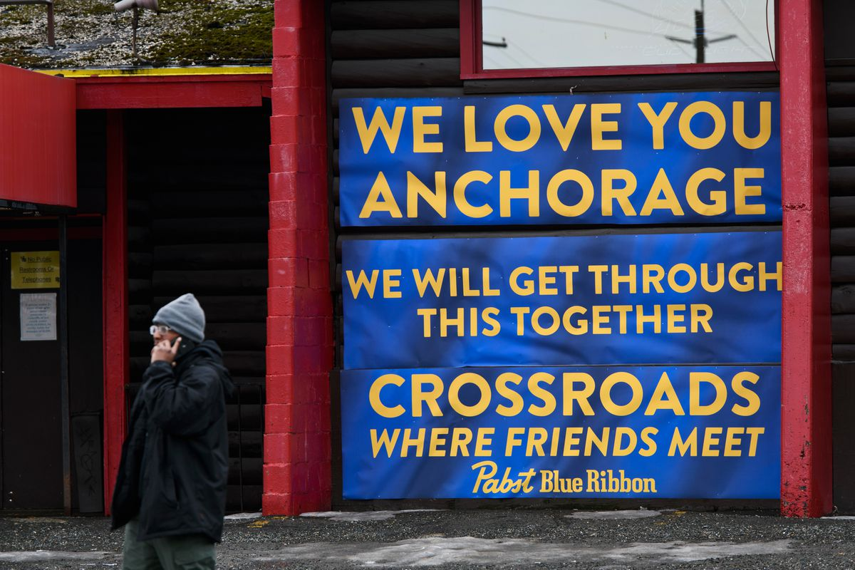 A sign hangs on the outside a closed Crossroads Lounge on April 16, 2020, in Anchorage. (Marc Lester / ADN)