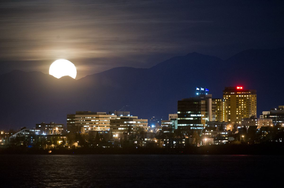 The moon, a day past full, rises over the Chugach Mountains and downtown Anchorage in this view from the Coastal Trail on Tuesday, November 15, 2016. (Marc Lester / Alaska Dispatch News)