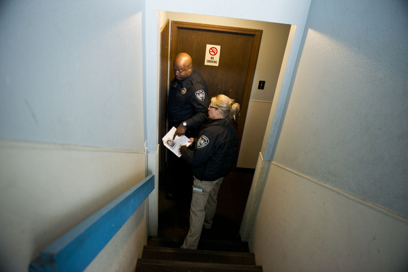 """Anchorage Police speak with the resident of an apartment building as they look for a man with an outstanding domestic violence-related warrant. APD served nine DV-related warrants Wednesday as part of the """"roundup"""" effort. (Marc Lester / Alaska Dispatch News)"""