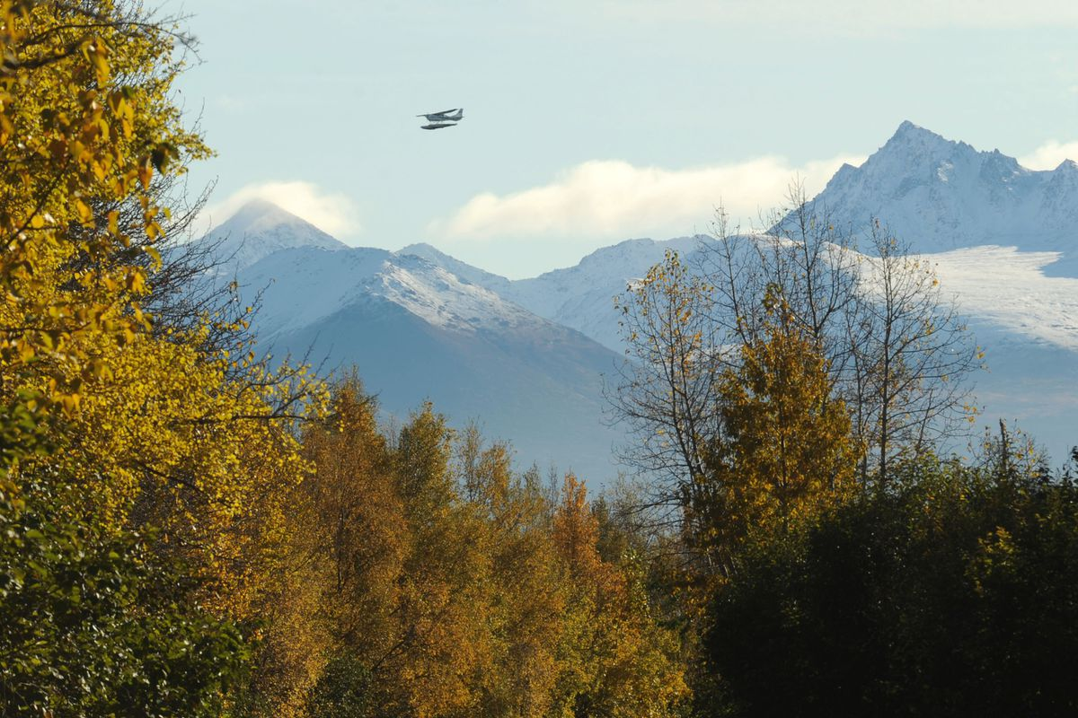 A floatplane flies through the scene as termination dust challenges fall colors for attention in a view from Point Woronzof Roadin October 2011. (Erik Hill / ADN archive)