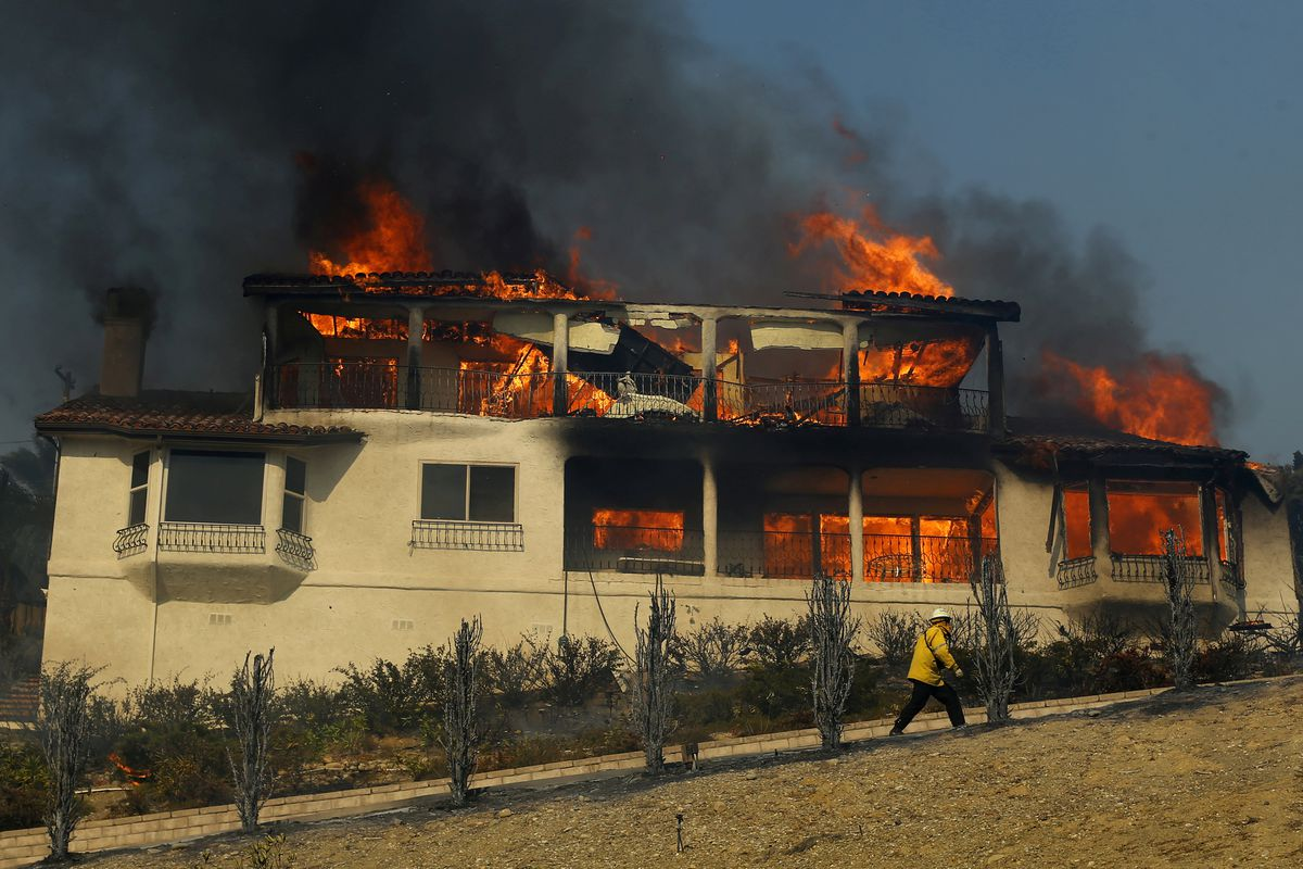 A firefighter inspects a burning home during a wind-driven wildfire in Ventura, California, Tuesday. REUTERS/Mike Blake