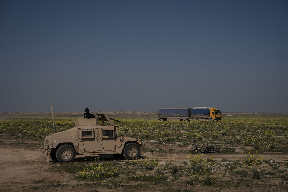 A U.S.-backed Syrian Democratic Forces Humvee stands by as a truck that is part of a convoy evacuating hundreds out of the last territory held by Islamic State militants, passes in Baghouz, eastern Syria, Wednesday, Feb. 20, 2019. (AP Photo/Felipe Dana)