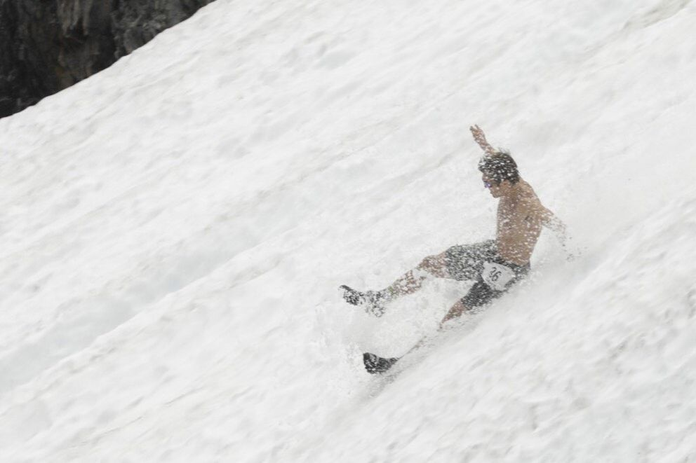 David Norris slides down the snow in the men's Mount Marathon race in Seward. (Loren Holmes / ADN)