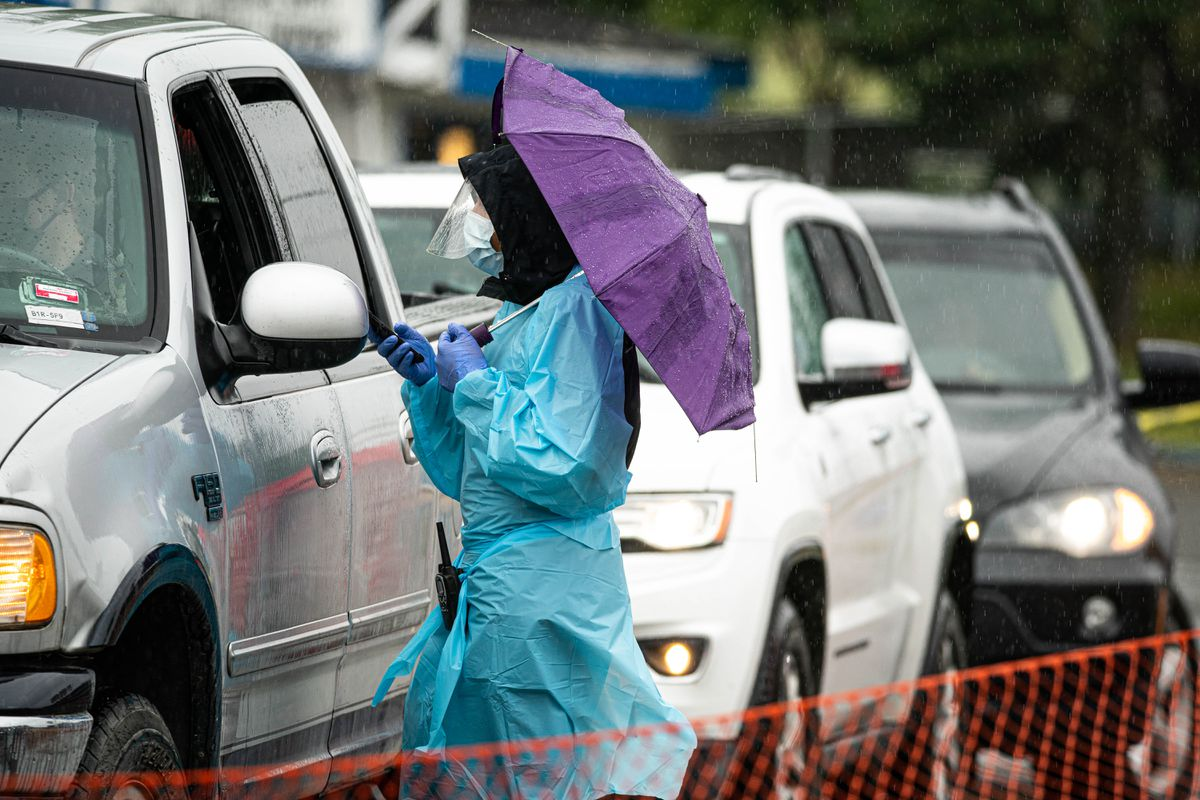 A healthcare worker uses an umbrella as they talk with people waiting in line at the Lake Otis Blvd COVID-19 testing site on Wednesday, July 8, 2020. The current weather forecast calls for rain through the weekend. (Loren Holmes / ADN)