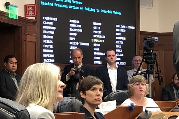 From left to right, Rep. Andi Story, D-Juneau; Rep. Ivy Spohnholz, D-Anchorage; and Rep. Sara Hannan, D-Juneau, watch as Sen. John Coghill, R-North Pole, delivers a speech Thursday, July 11, 2019 in a joint session of the Alaska Legislature. (James Brooks / ADN)