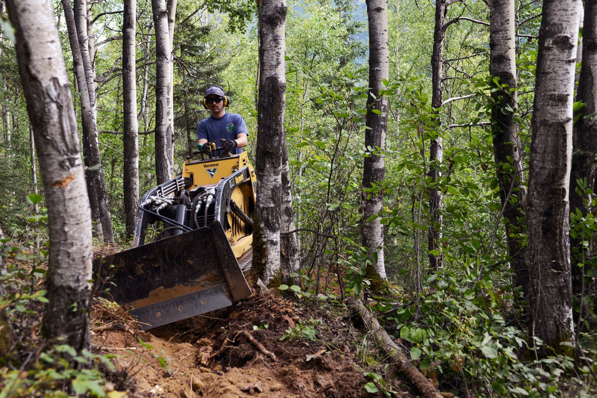 Ed Kessler of Ptarmigan Ptrails works to punch through a challenging stretch of singletrack trail with a mini bulldozer Tuesday afternoon, August 16, 2016, on the north side of Mirror Lake. (Erik Hill / Alaska Dispatch News)