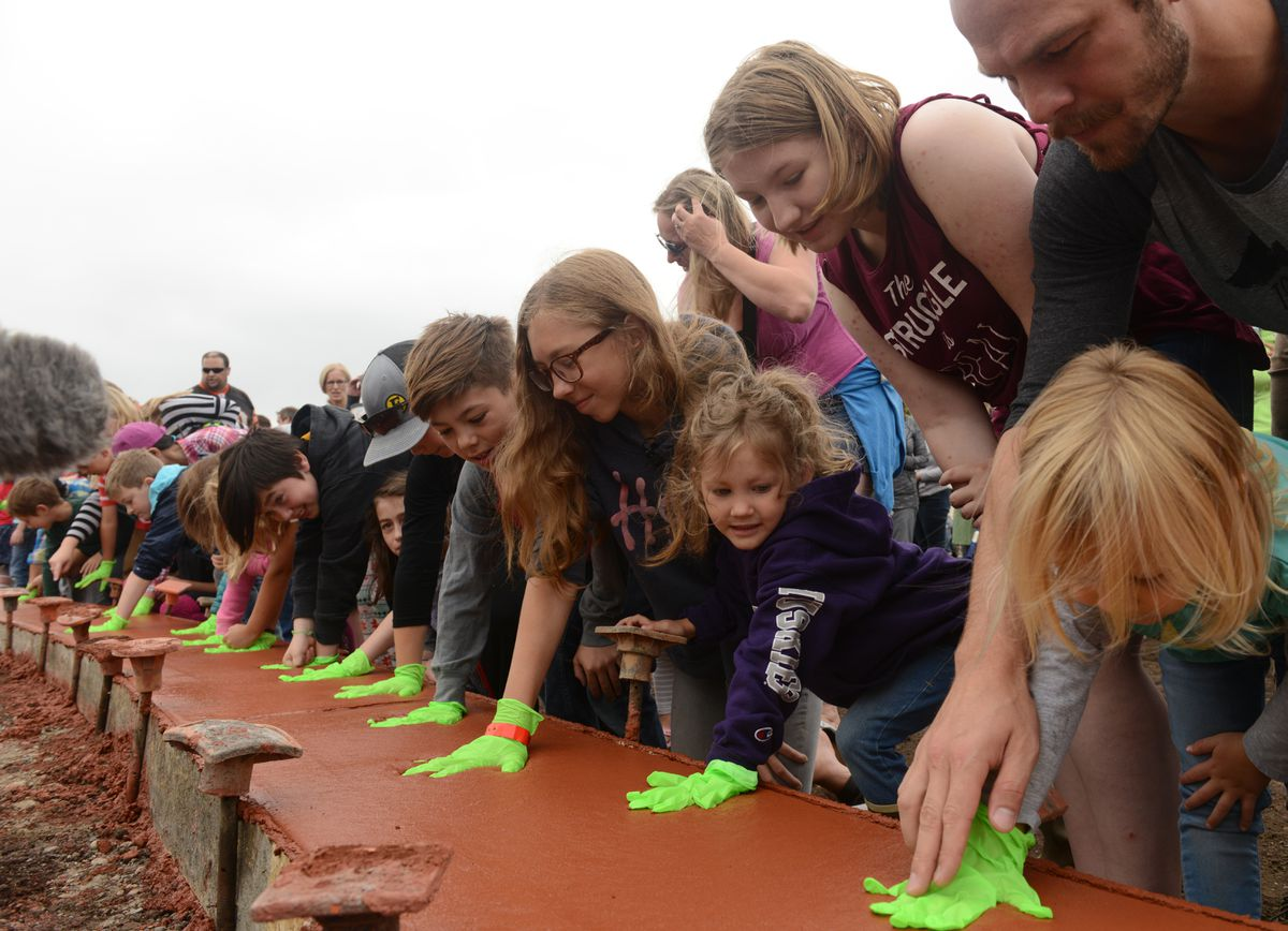 Kids had the first chance to leave their handprints in a curving ribbon of red concrete along Spenard Road in Anchorage on Saturday. (Bob Hallinen / ADN)
