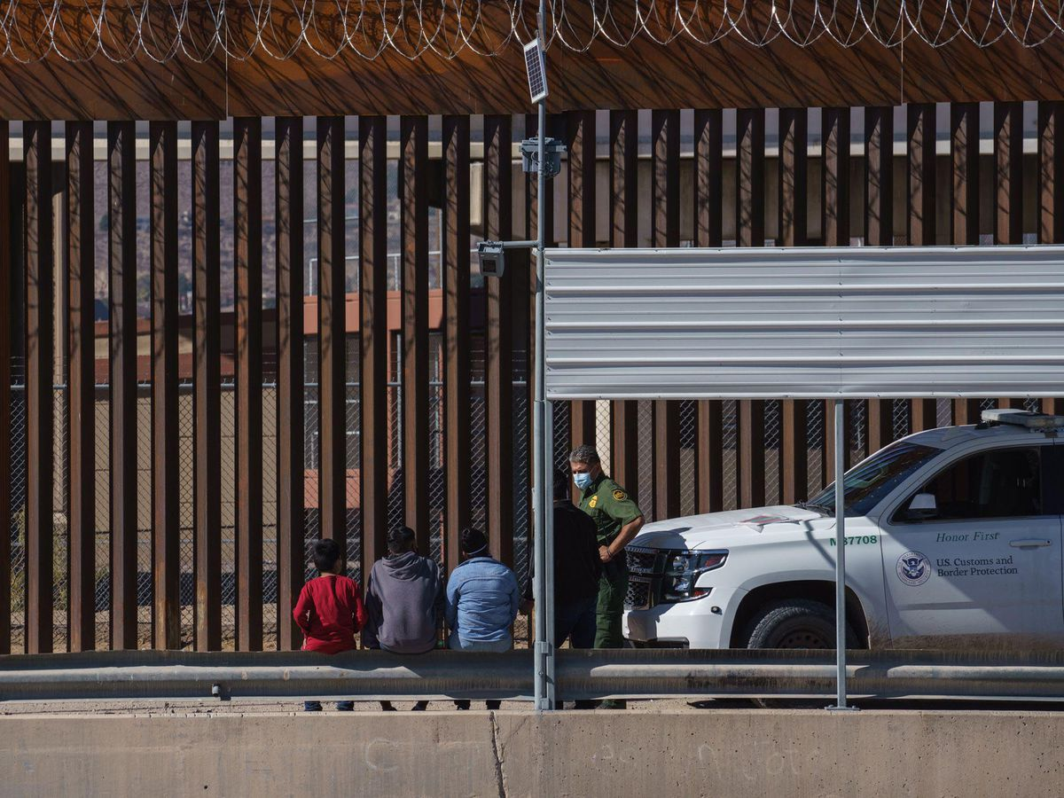 A U.S. Border Patrol officer speaks to migrants in El Paso, Texas, after they crossed the U.S. and Mexico border wall seen from Cuidad Juarez, Mexico, on Feb. 11, 2021. (Bloomberg photo by Raul Ratje)