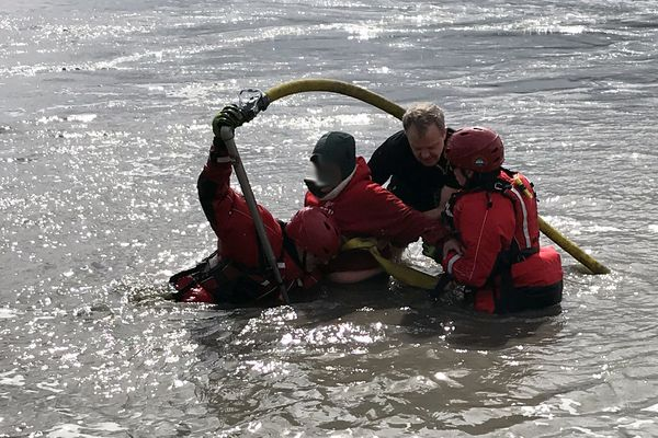 Rescuers use a tool to free a woman stuck in mud on the Turnagain Arm on Friday. Photo courtesy of Girdwood Fire Department, which blurred the unidentified woman's face.
