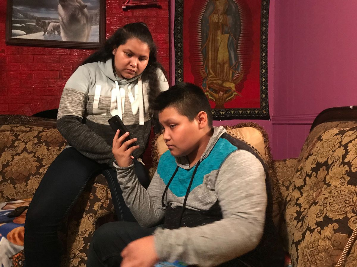 Juana Andres, 12, and Eduardo Andres, 14, take a call from a relative as they wait for news of their mother and father, who were detained by federal immigration officials at their workplace in Morton, Miss., on August 7, 2019. (Jenny Jarvie/Los Angeles Times/TNS)