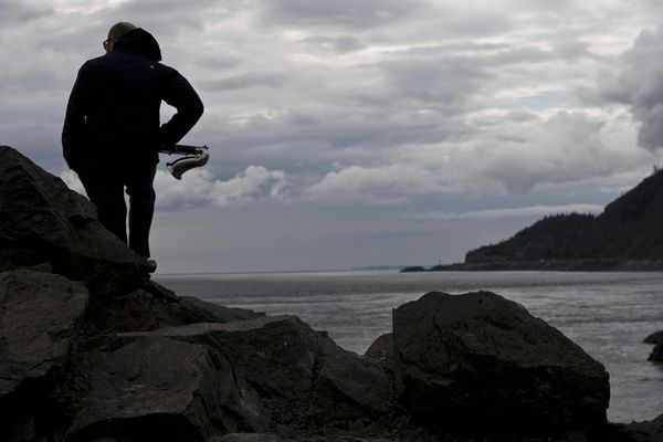 Garrett Burtner holds his bass clarinet at Beluga Point. The EcoSono Festival of Environmental Sound Art began at Beluga Point on Turnagain Arm on Wednesday, July 26, 2017. Wind, string and percussion musicians accompanied the amplified sound of the incoming tide with underwater microphones offshore to create a unique sound. The festival continues through July 29 with events outside the Anchorage Museum, at the Church of Love in Spenard and at the International Gallery of Contemporary Art. EcoSound is founded and directed by Matthew Burtner of Anchorage. (Marc Lester / Alaska Dispatch News)