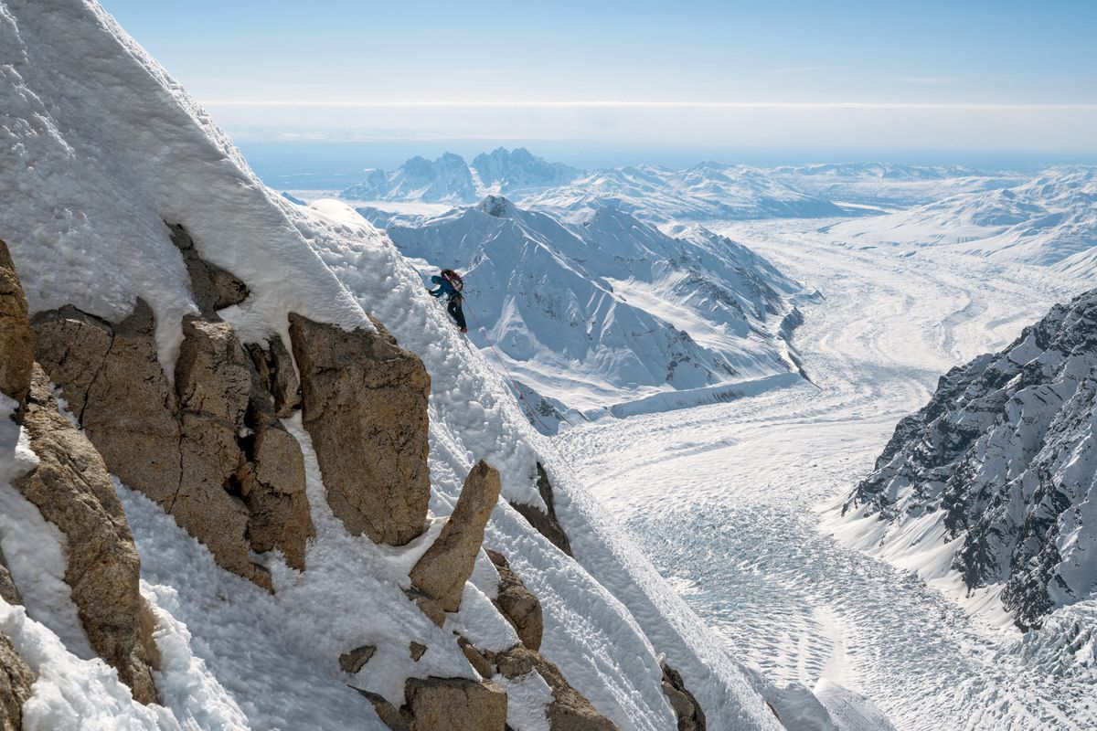 Jess Roskelley traverses toward the Third Tower on day three of the climb of Mount Huntington via the South Ridge in late April. Often Roskelley and partner Clint Helander would finish a pitch lower than they had started due to the traversing nature of the ridge. The Tokosha Mountains rise in the distance. (Photo by Clint Helander)