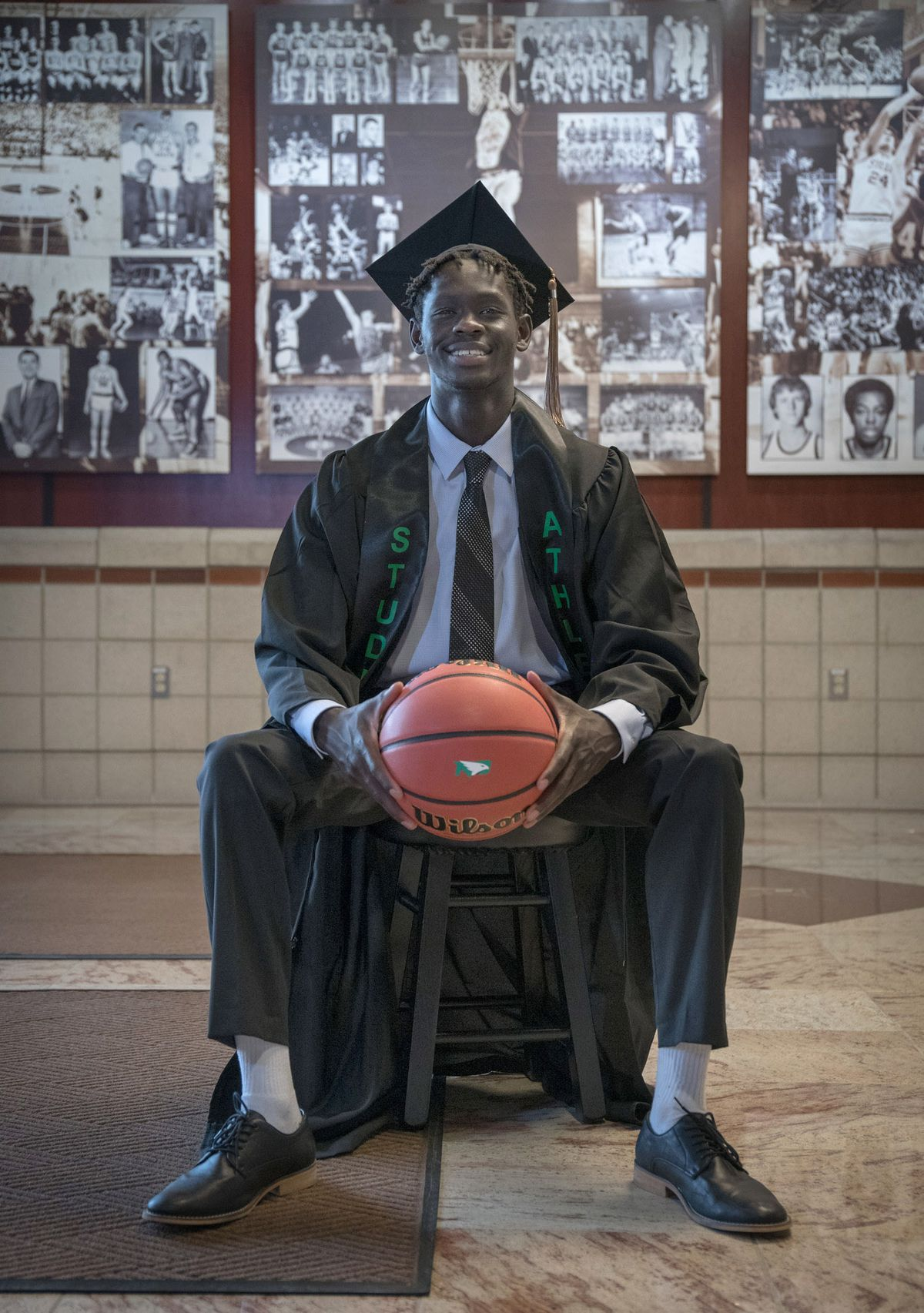 Bentiu Panoam of Anchorage wears his cap and gown after becoming the first person froom his family to graduate from college in May 2021. Panoam, who attended the University of North Dakota on a basketball scholarship, is the son of Sudanese refugees and one of 10 children in his family. (Photo by Crystal Saddler)
