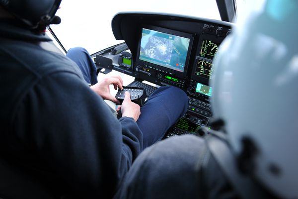 Tactical flight officer Zac Johnson monitors the new camera and mapping system onboard an Alaska Department of Public Safety helicopter during a demonstration on March 12, 2019. (Photo courtesy Alaska Department of Public Safety.)