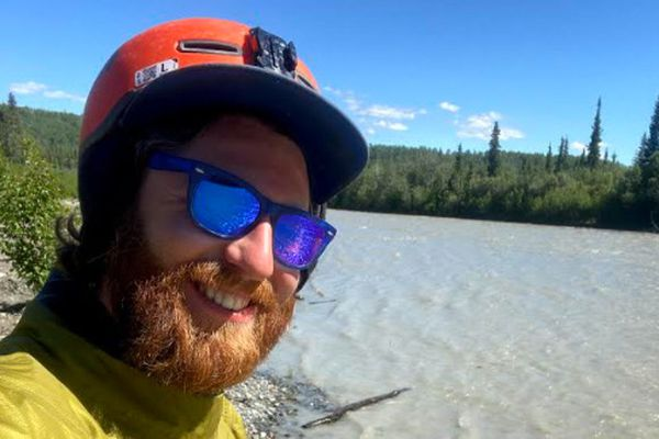 Wil Brown of Anchorage stands near his packraft at the Gakona River on Thursday, July 1, 2021, a day after he paraglided nearly 100 miles from Sheep Mountain Lodge to a river island about 15 miles from Gakona. (Wil Brown photo)