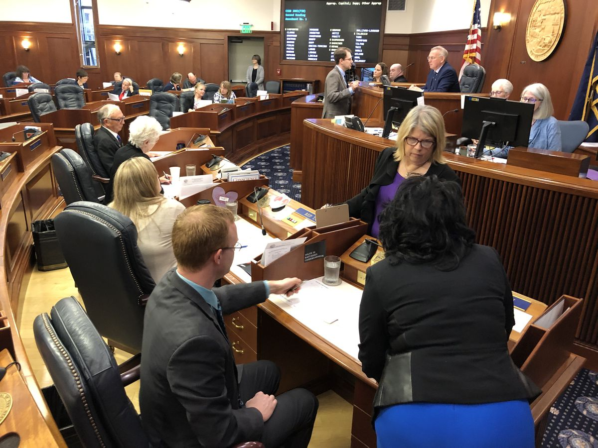 Rep. Tammie Wilson, R-North Pole (standing, in purple) discusses a proposed amendment with Rep. David Eastman, R-Wasilla (seated) and Rep. Cathy Tilton, R-Wasilla (standing, in blue) on Sunday, July 21, 2019. (James Brooks / ADN)