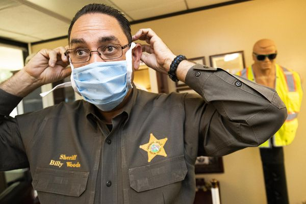 Sheriff Billy Woods demonstrates a mask made by inmates at the Marion County Jail in April. Woods issued orders Tuesday forbidding his employees from wearing masks on the job in most circumstances, with the jail being an exception. [Doug Engle/Ocala Star-Banner]