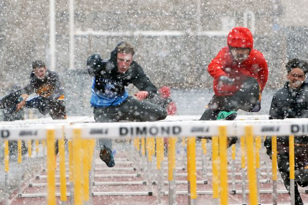 Competitors in the boys 110 meter hurdles race battle through the snow during a four-team track and field meet on Wednesday, April 17, 2019 at Dimond Alumni Field. (Matt Tunseth / Chugiak-Eagle River Star)