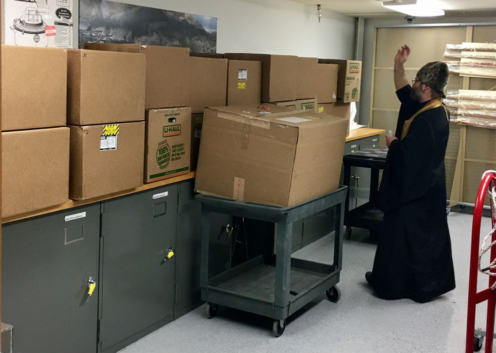 Father Innocent Dresdow blesses boxes containing the remains of Kodiak Alutiiq people from Chirikof Island in a storage room at the Alutiiq Museum on Thursday. (April Laktonen Counceller / Alutiiq Museum)