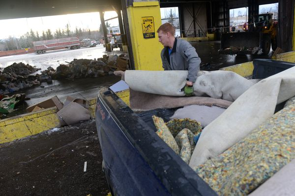 Rex Talcott unloads carpet and carpet backing at the midtown transfer station in Anchorage, AK on Saturday, Dec. 1, 2018 after a 7.0 earthquake on Friday. Talcott's in-law's 4-plex suffered major water damage and the foundation sunk about 8 inches. (Bob Hallinen / ADN)