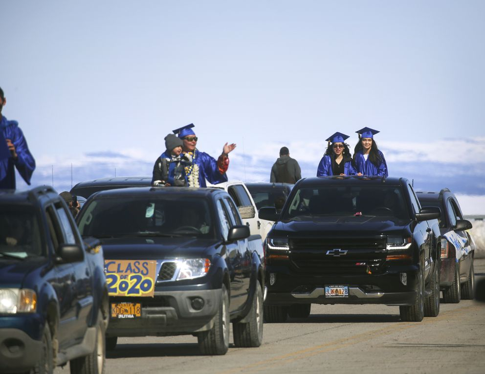 Kotzebue High School seniors stand in the beds of decorated trucks and wave to residents gathered along Third Avenue during a senior graduation parade in Kotzebue on Saturday, May 2, 2020. (Photo by Emily Mesner)