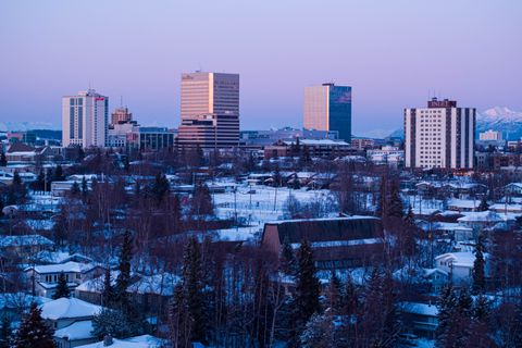 The setting sun illuminates buildings in downtown Anchorage on Wednesday, March 3, 2021. (Loren Holmes / ADN)