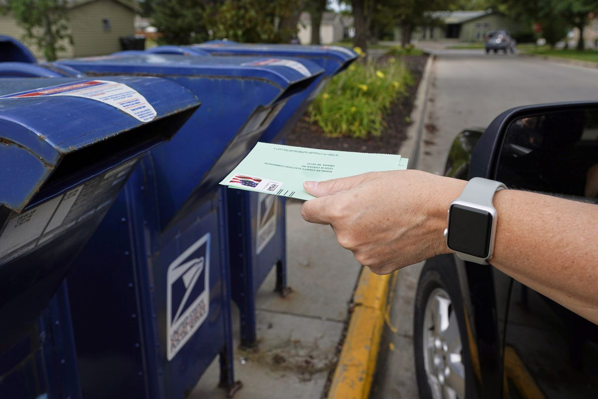 FILE - In this Tuesday, Aug. 18, 2020, file photo, a person drops applications for mail-in-ballots into a mail box in Omaha, Neb. (AP Photo/Nati Harnik, File)