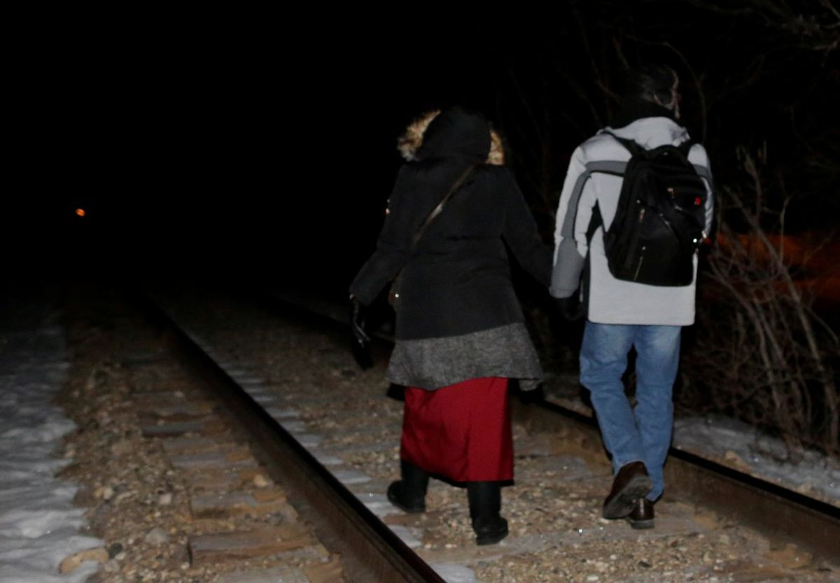 Refugees walk along railway tracks from the United States to enter Canada at Emerson, Manitoba, Canada February 26, 2017. REUTERS/Lyle Stafford