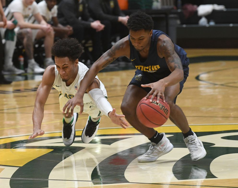DeAndre Osuigwe of UAA and Psalm Maduakor of Billings go for a loose ball. (Photo by Bob Hallinen)
