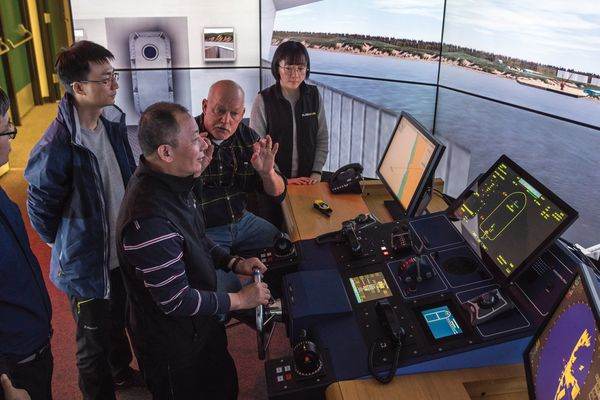 Visitors representing Chinese state-owned corporations interested in the Alaska LNG Project took a few turns at the helm of a giant LNG tanker docking at Nikiski with the marine simulator at the AVTEC trade school in Seward. (Photo/Courtesy/Alaska Gasline Development Corp.)