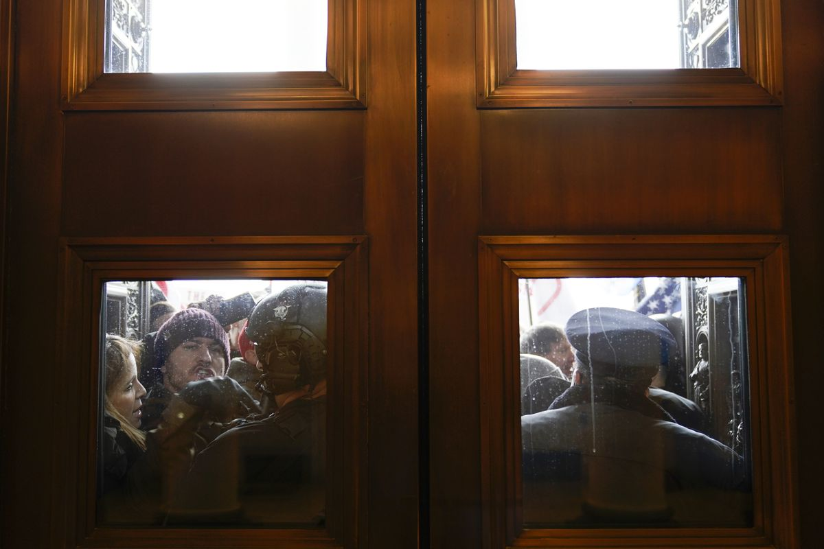 U.S. Capitol Police try to hold back protesters outside the east doors to the House side of the U.S. Capitol, Wednesday, Jan 6, 2021. (AP Photo/Andrew Harnik)
