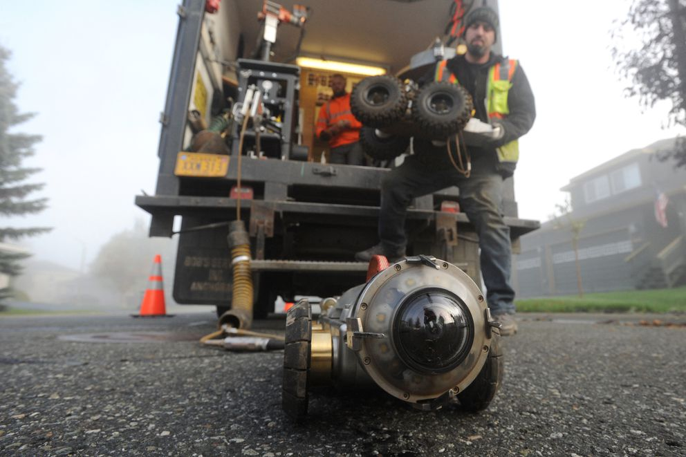 City street maintenance workers prepare to document the condition of a 12-inch storm drain in the Southport subdivision with a remote camera on Thursday, Oct. 3, 2019. (Bill Roth / ADN)
