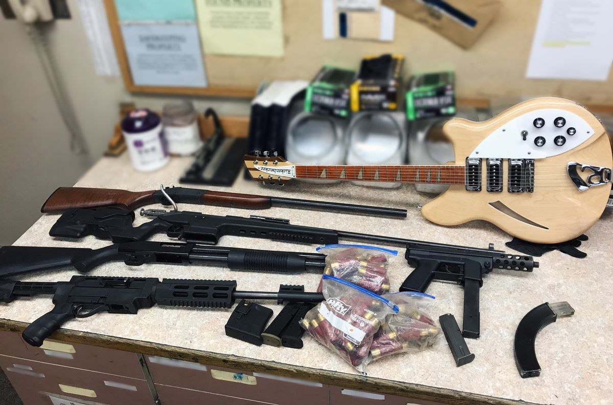 At the home of vehicle theft suspect Kyle Paye, officers found a license plate from a stolen car and five guns plus a stolen guitar. (Anchorage Police Department photo)