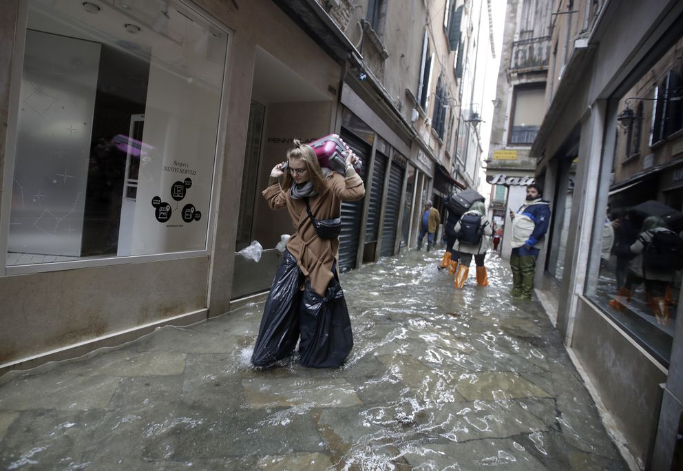 A woman wears bin bags as she carries her suitcase while wading through high water, in Venice, Wednesday, Nov. 13, 2019. The high-water mark hit 187 centimeters (74 inches) late Tuesday, Nov. 12, 2019, meaning more than 85% of the city was flooded. The highest level ever recorded was 194 centimeters (76 inches) during infamous flooding in 1966. (AP Photo/Luca Bruno)