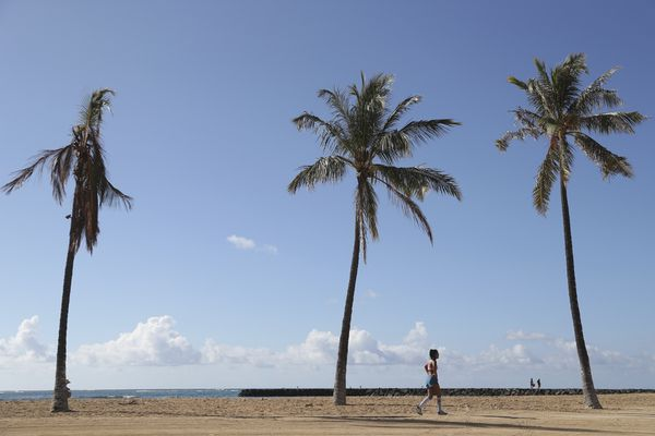 A beachgoer walks down Waikiki Beach, Thursday, Oct. 15, 2020, in Honolulu. A new pre-travel testing program will allow visitors who test negative for COVID-19 to come to Hawaii and avoid two weeks of mandatory quarantine goes into effect Thursday. The pandemic has caused a devastating downturn on Hawaii's tourism-based economy and many are hoping the testing will help the economy rebound. (AP Photo/Marco Garcia)