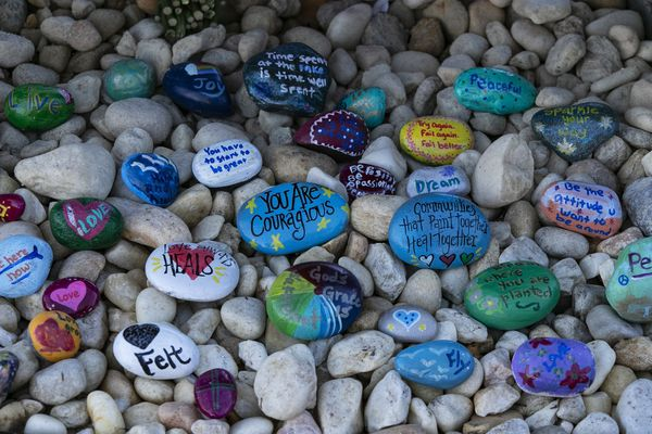 Stones are placed at a memorial outside Marjory Stoneman Douglas High School during the one-year anniversary of the school shooting, Thursday, Feb. 14, 2019, in Parkland, Fla. A year ago on Thursday, 14 students and three staff members were killed when a gunman opened fire at the high school. (Al Diaz/Miami Herald via AP)