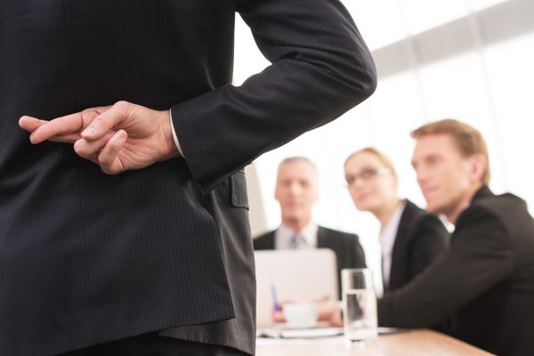Rear view of man in formalwear keeping fingers crossed behind his back while three people sitting on background. (Thinkstock)