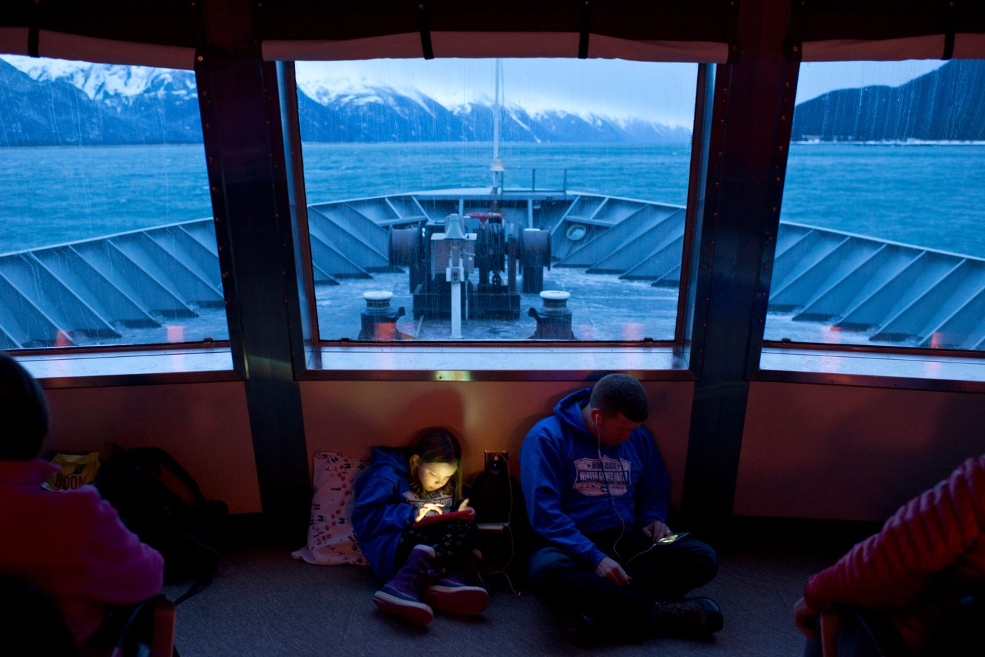 Passengers on a crowded ferry headed from Haines to Juneau make use of their devices on January 22, 2017. (Marc Lester / Alaska Dispatch News)