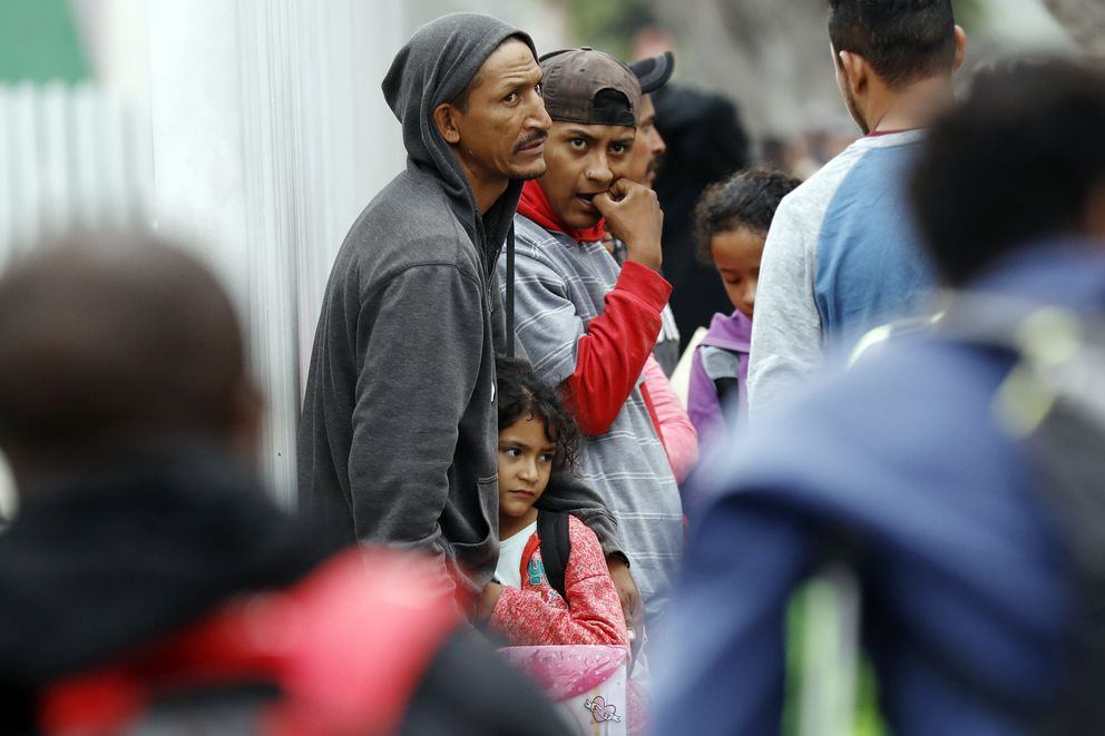 FILE - In this July 16, 2019, file photo, people wait to apply for asylum in the United States along the border in Tijuana, Mexico. A federal judge rules that the Trump administration is operating within its authority when separating families stopped at the Mexican border, rejecting arguments that it was quietly returning to widespread practices that drew international condemnation. (AP Photo/Gregory Bull, File)