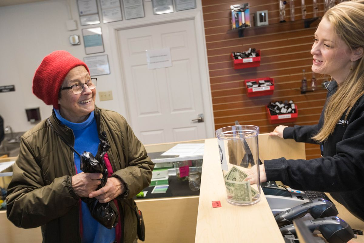 Kameron Kowalski sells a 2.5-gram container of marijuana to Anna Ercoli, 80, the first customer in line at Arctic Herbery on Thursday, Dec. 15, 2016. Arctic Herbery was the first legal marijuana retail store to open in Anchorage, Alaska's largest city. (Loren Holmes / Alaska Dispatch News)