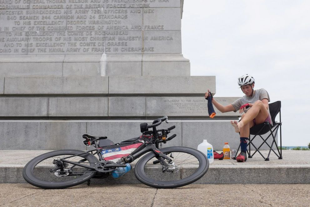 Cyclist Lael Wilcox of Anchorage removes her socks for the first time in three days after arriving in Yorktown, Virginia. (Nicholas Carman)