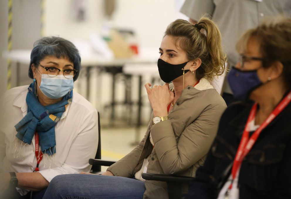 Claire Shaw, campaign manager for Forrest Dunbar, sits with Katherine Pfeiffer, left, as they observe election workers count ballots on the second day of vote counting at the MOA Election Center in Anchorage on Wednesday, May 12, 2021. (Emily Mesner / ADN)