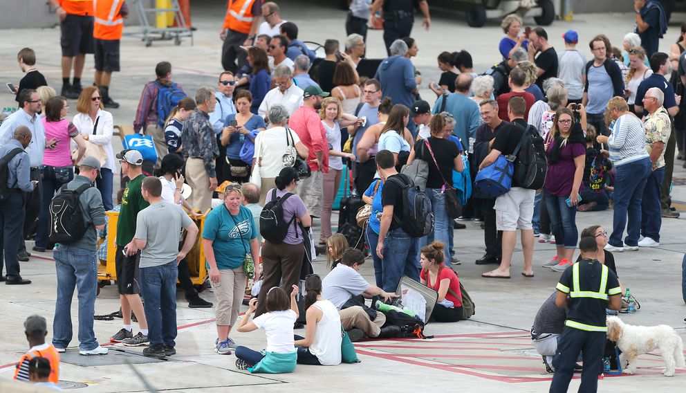 Passengers on the tarmac as authorities said multiple people have died after a lone suspect opened fire at the Ft. Lauderdale-Hollywood International Airport on Friday, Jan. 6, 2017, in Fort Lauderdale, Fla. (David Santiago/El Nuevo Herald/TNS)