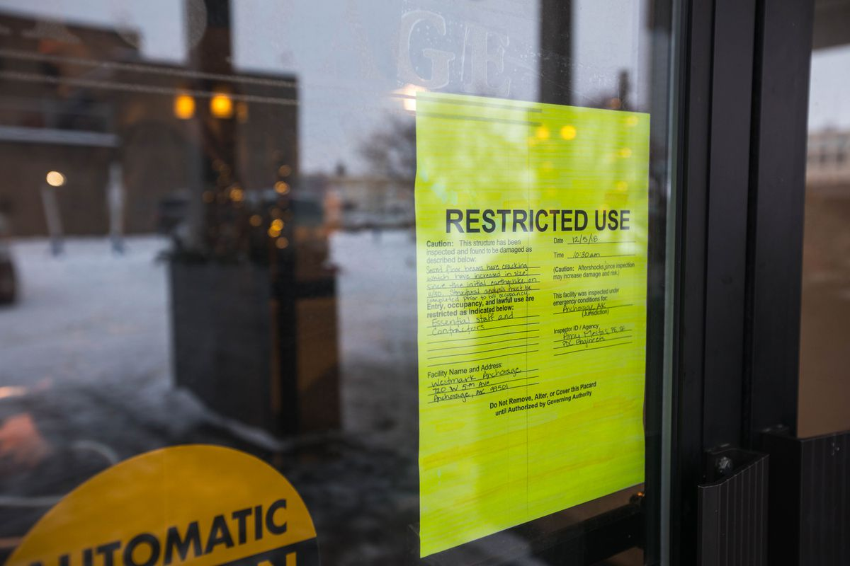 A yellow tag, indicating restricted use, is affixed to the door of the Westmark Hotel in downtown Anchorage on Friday. The tag states that