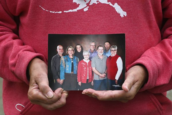 Jeanne Grasser holds a photograph of her mother Marilyn Grasser, center, who is surrounded by her son and two daughters and their spouses and a grandson. Marilyn Grasser is a resident at the Alaska Veterans and Pioneers Home in Palmer. (Bill Roth / ADN)