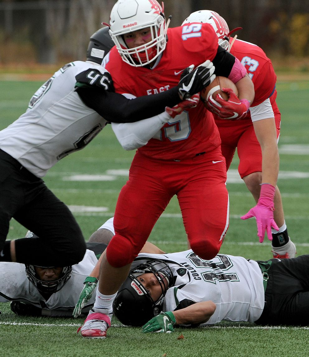 East's Orson Fitiausiis driven out of bounds by Colony's Ryan Murphy after breaking free from Julian McPhail and Ridge Raval at East High on Saturday. (Bob Hallinen / ADN)